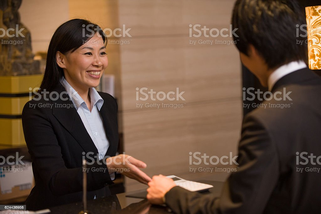 Asian Concierge no Hotel com o cliente - foto de acervo