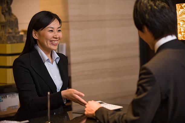アジアのホテルのコンシェルジュが、顧客 - 受付係 ストックフォトと画像