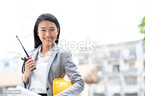 1129095769 istock photo Asian confident engineer women holding radio equipment work safety and protection control at construction site industry, engineer project development concept 1130106369