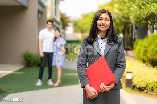Asian confident woman real estate agent or realtor in suit holding red file and smile with young couple home sellers behind in front of house. Portrait of a lovely female broker.