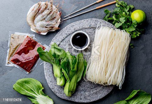 istock Asian cooking ingredients: rice noodles, pok choy, sauces, raw shrimps. Asian food concept Chinese or Thai cuisine. 1161512474