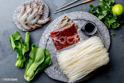 istock Asian cooking ingredients: rice noodles, pok choy, sauces, raw shrimps. Asian food concept Chinese or Thai cuisine. 1161512646
