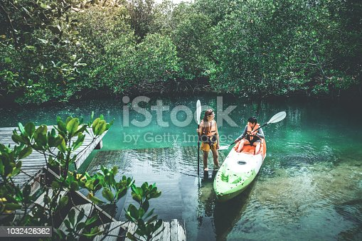 Asian couple adventure with Kayaks in Beautiful mangrove forest Lagoon vacation time