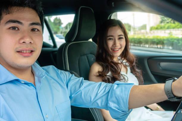 asiatische paar fahren in einem auto für testfahrt vor dem kauf neues auto, - klavier verkaufen stock-fotos und bilder
