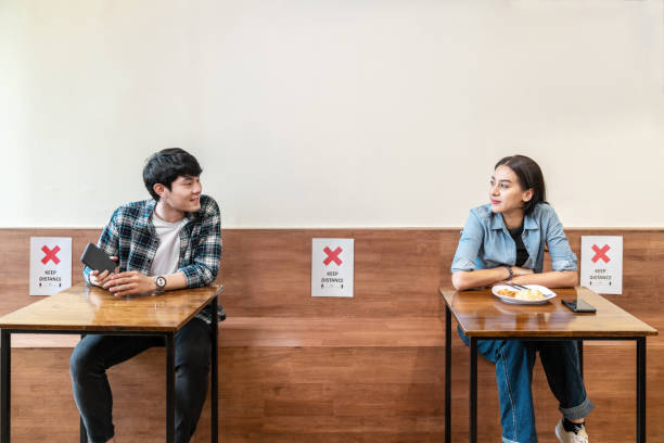 Asian couple at seat and keep distance potocol paper sign on seat at reopenning restaurant. Arrangement blank space table to prevent and stop coronavirus by social distancing after lockdown measure. stock photo