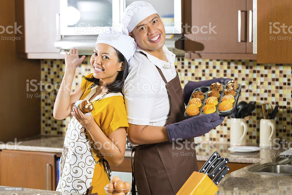 Asian couple baking muffins in home kitchen royalty-free stock photo