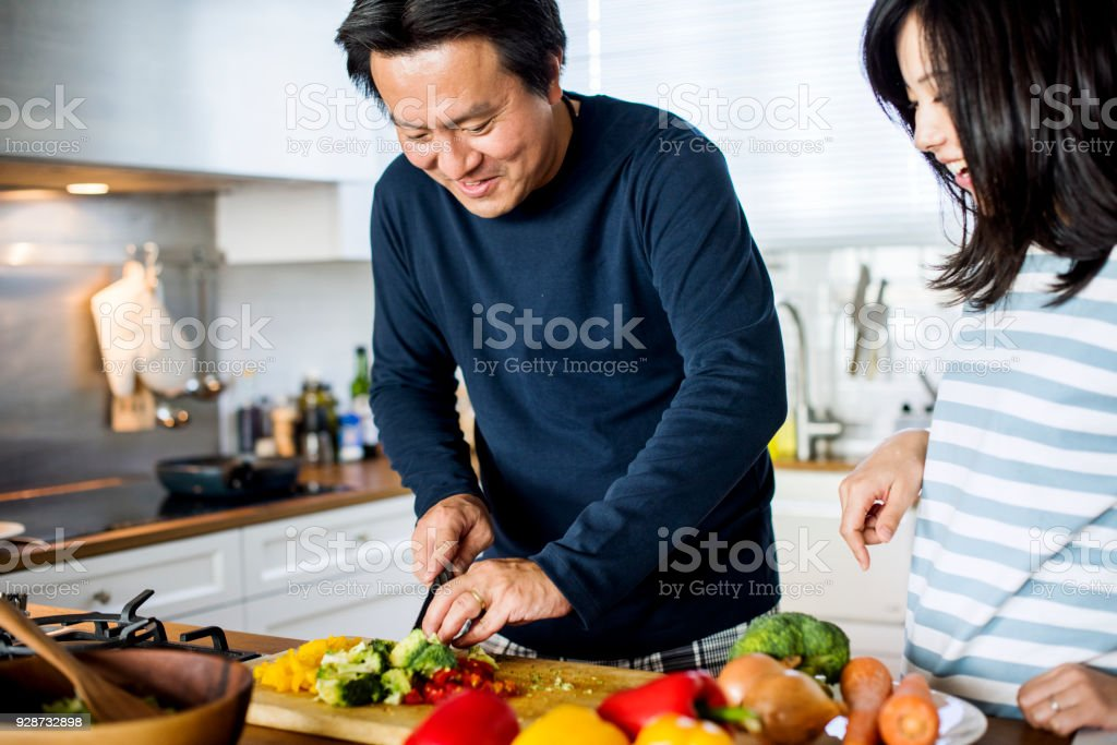 Asian couple cooking in the kitchen stock photo