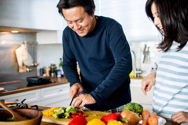 Asian couple cooking in the kitchen Asian couple cooking in the kitchen preparing food stock pictures, royalty-free photos & images