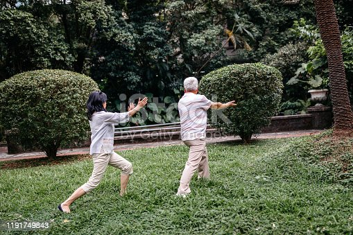 646614234 istock photo Asian couple doing exercises in public park 1191749843