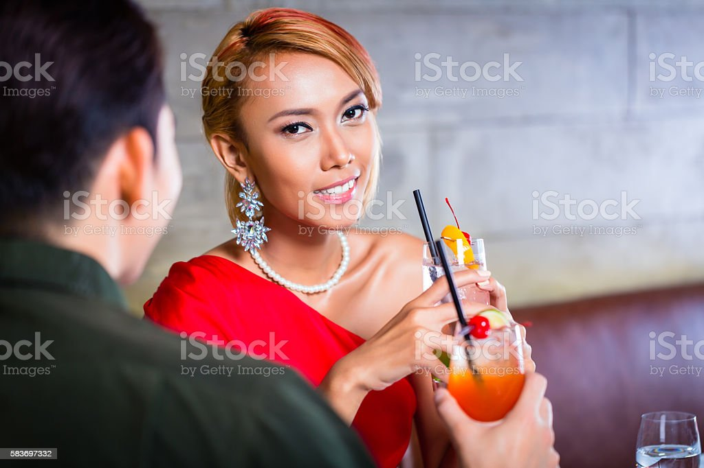 Asian couple drinking cocktails in fancy bar stock photo