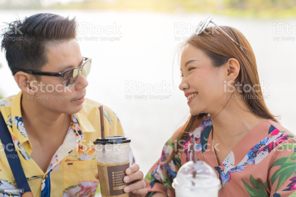 Asian couple drinking coffee and smileing on river background. zbiór zdjęć royalty-free