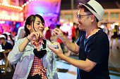 Asian couple enjoy eating on the street food at Khao San road.