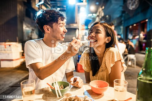 Asian couple enjoying street food in Hong Kong