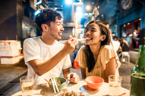 Asian couple enjoying street food in Hong Kong Asian couple enjoying street food in Hong Kong date night romance stock pictures, royalty-free photos & images
