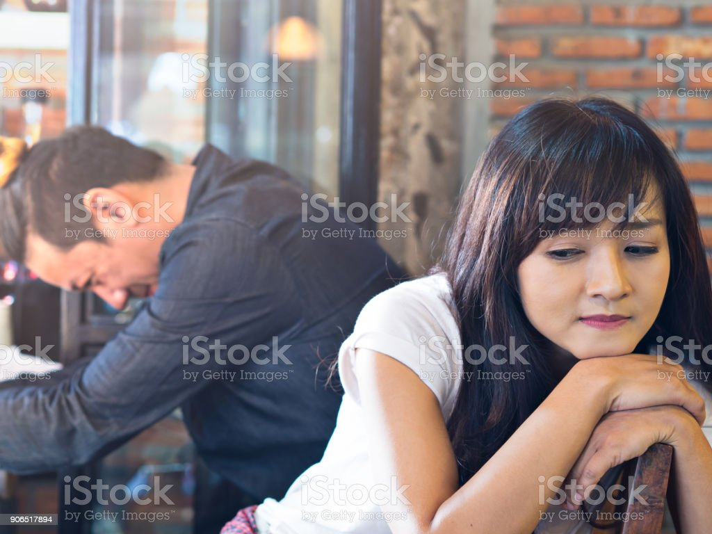 Asian couple feeling upset after quarrel in coffee shop, cafe or restaurant at dating, broken heart concept stock photo