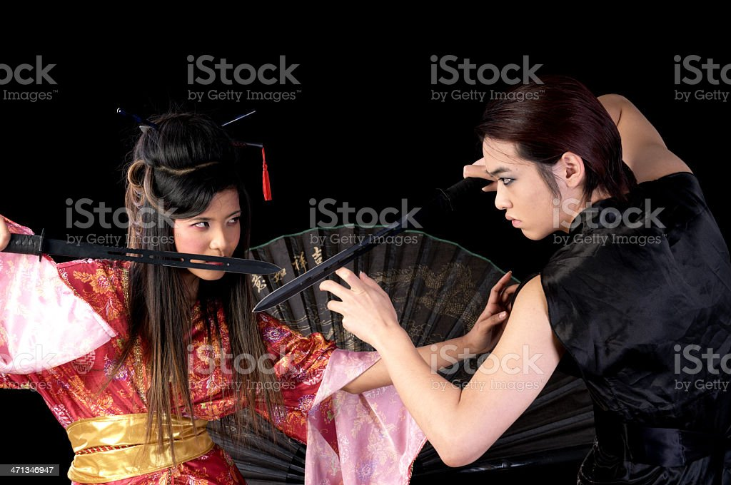 Asian couple fighting with swords. royalty-free stock photo