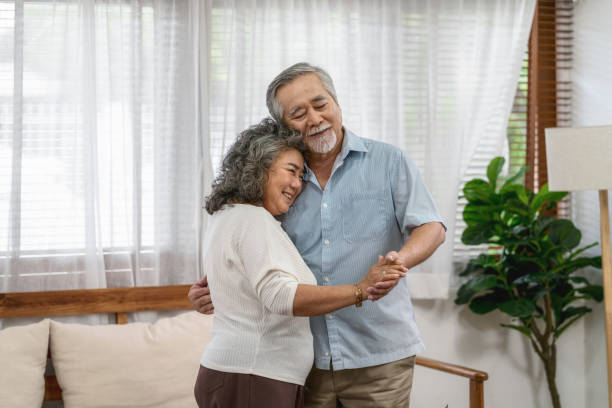 Asian couple Grandparent dancing and hugging together with happy feeling in house