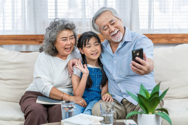 Asian couple Grandparent taking selfie with Granddaughter