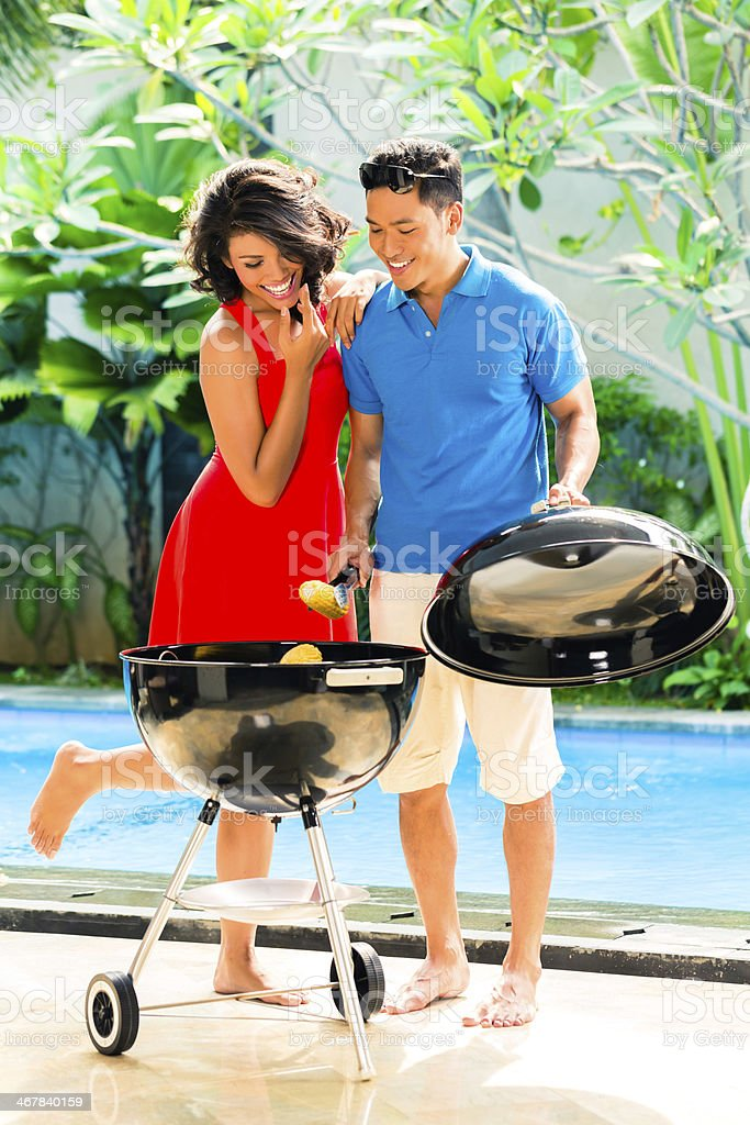 Asian couple having barbecue at the pool stock photo