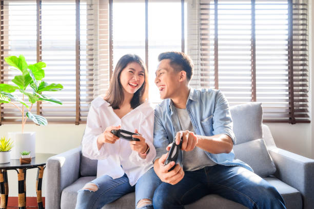 asian couple having fun play video games together - man joystick imagens e fotografias de stock