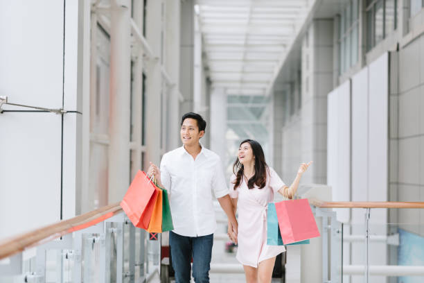 Asian couple holding colorful shopping bags and enjoying shopping Happy Asian couple holding colorful shopping bags and enjoying shopping, having fun together in mall. Consumerism, love, dating, lifestyle concept shopping couple asian stock pictures, royalty-free photos & images