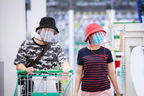 pareja asiática en DIY escudo facial y máscara facial médica de compras en supermarket.covid-19 propagando brote - foto de stock