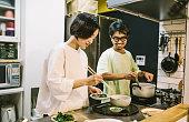 キッチンで食べ物を準備するアジアのカップル