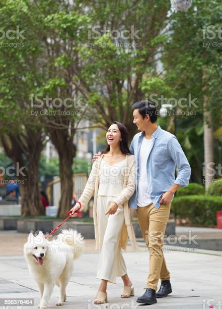 Asian couple laughing while walking dog outdoor in garden picture id898376464?b=1&k=6&m=898376464&s=612x612&h=fhkqqjwd6znn6ui73nmujzykzeuzudjdvxn rostkyi=