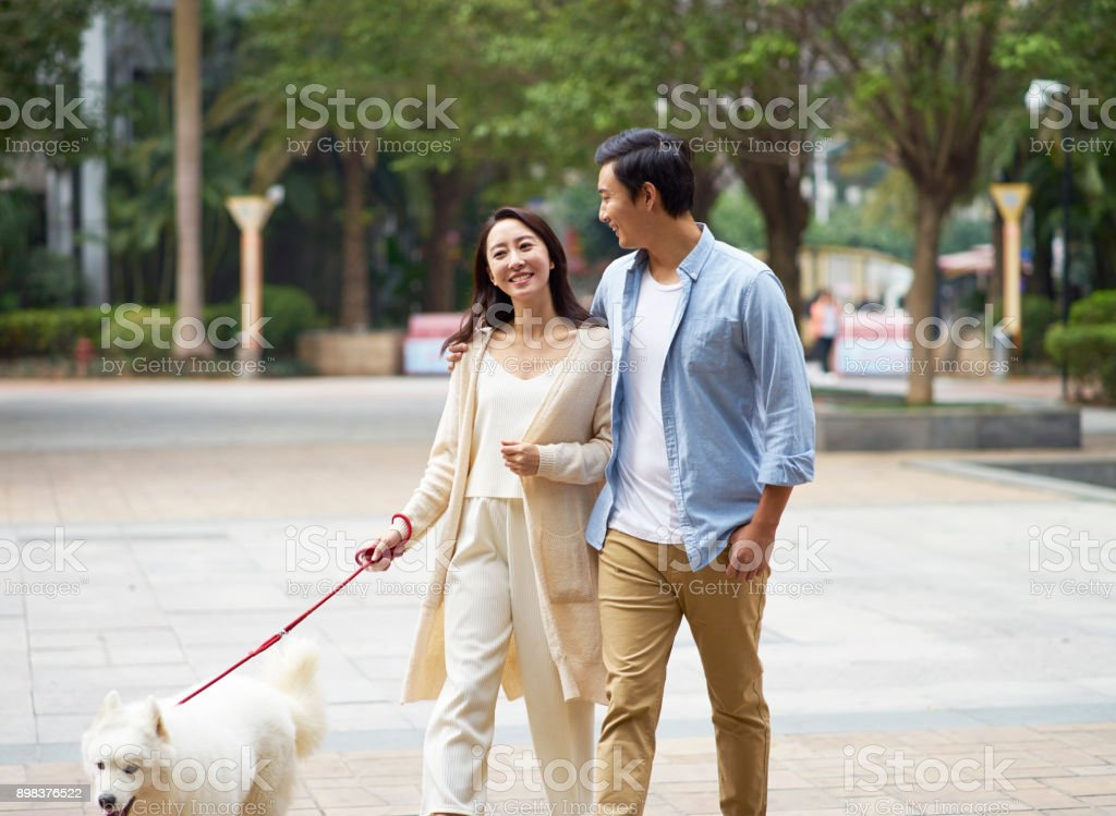 Asian couple laughing while walking dog outdoor in garden stock photo