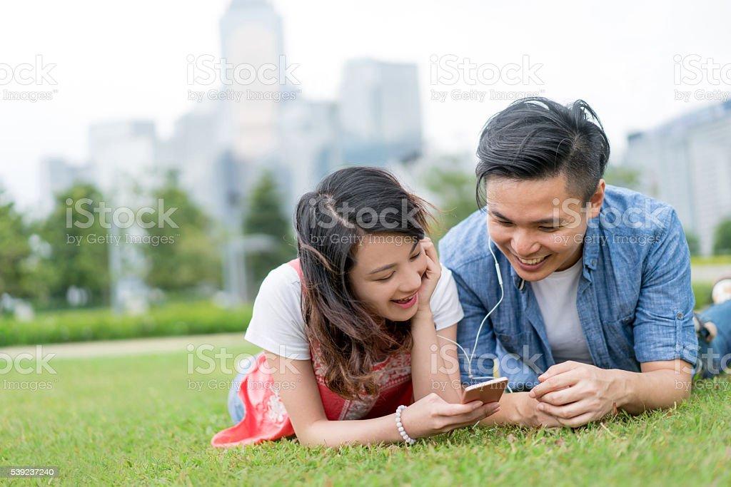 Asian couple listening to music at the park foto de stock libre de derechos