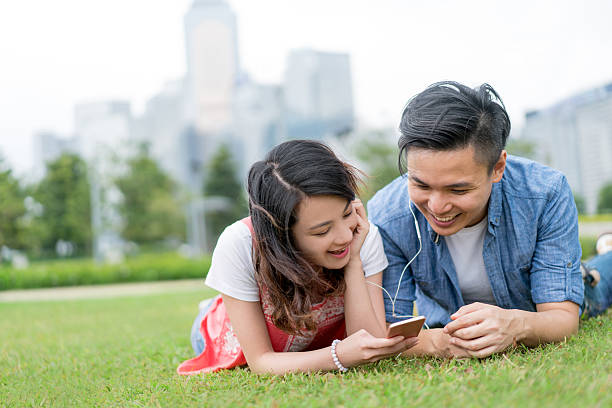 asian couple listening to music at the park - mp4 fotografías e imágenes de stock
