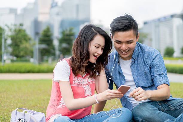 asian couple listening to music outdoors - mp4 fotografías e imágenes de stock