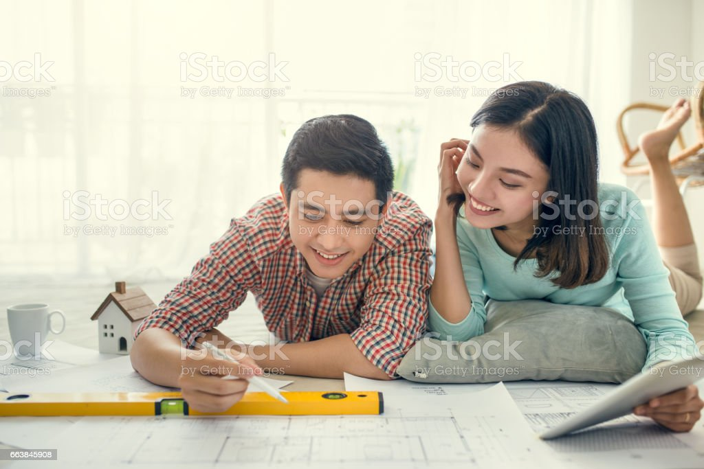 Asian couple looking at blueprint at home stock photo