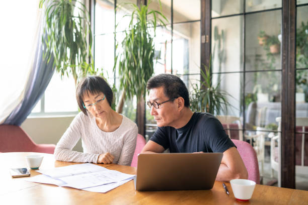 Asian couple looking at blueprints of their new house stock photo