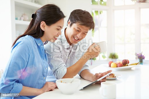 istock Asian Couple Looking At Digital Tablet Over Breakfast 494897227