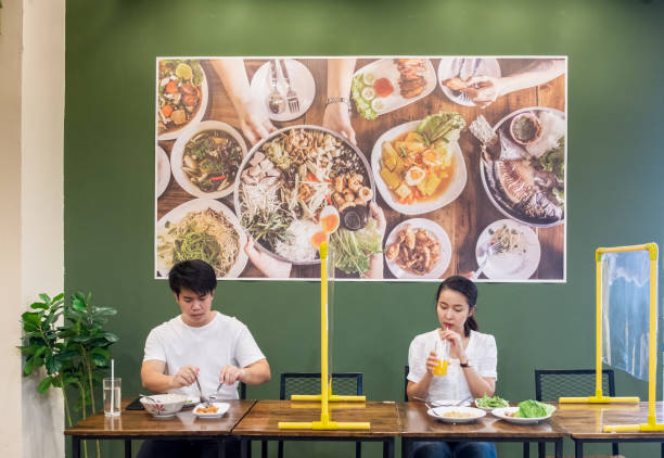 Asian couple man and woman sitting in restaurant eating food with table shield to protect infection from coronavirus covid-19, restaurant and social distancing concept stock photo