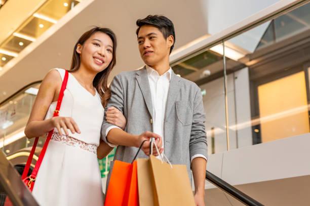 Asian Couple on an Escalator in a Shopping Mall stock photo