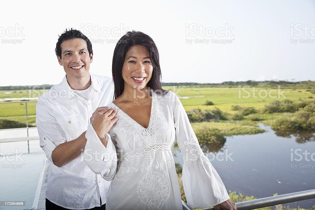 Asian couple on terrace overlooking marsh royalty-free stock photo