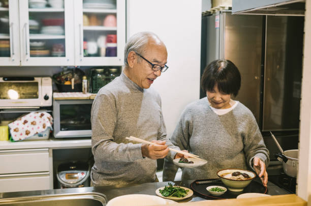Asian Couple preparing food in the kitchen stock photo
