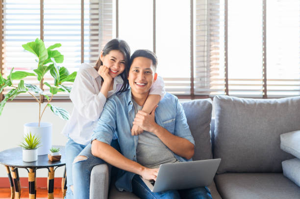 Asian couple relaxing on sofa while using laptop at home stock photo