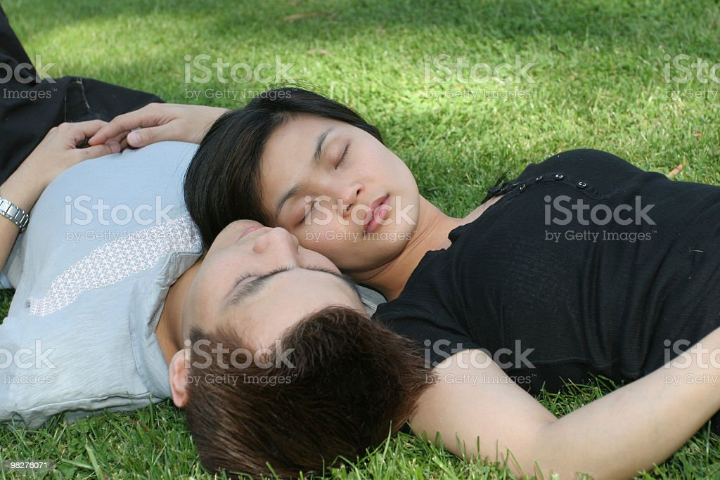Asian couple resting on the grass royalty-free stock photo