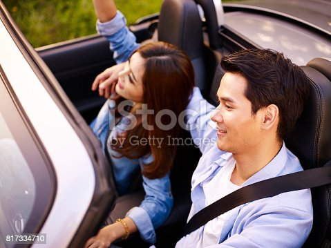 817334706 istock photo asian couple riding in a sports car 817334710