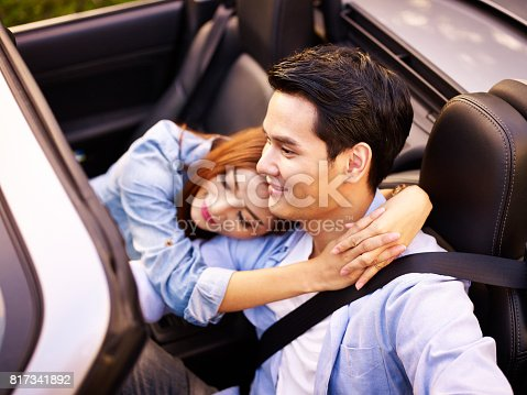 817334706 istock photo asian couple riding in a sports car 817341892