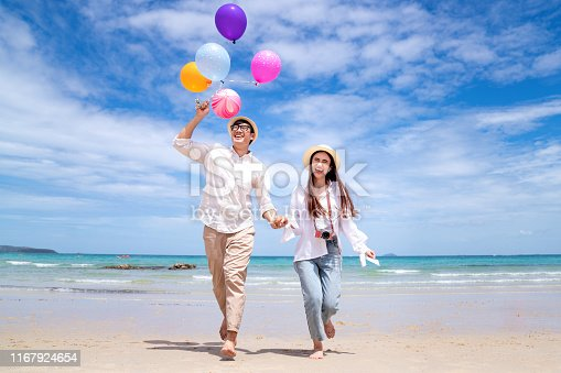 Asian couple run and happy on Pattaya beach with balloon on hand, Thailand, this image can use for travel, love, sweet, summer and valentine concept