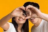 オレンジ色の背景に愛のサインを示すアジアのカップル