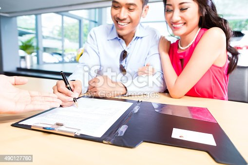 istock Asian Couple signing sales contract for car at dealership 490127760