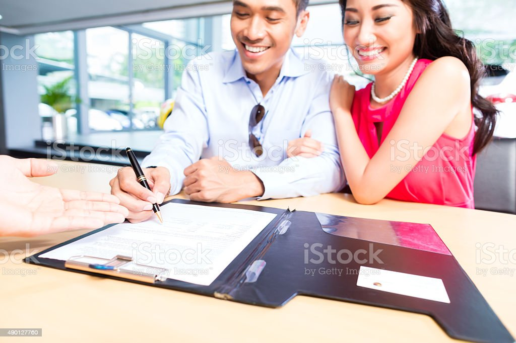 Asian Couple signing sales contract for car at dealership stock photo
