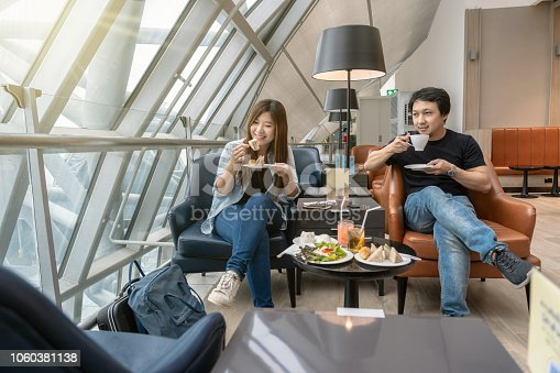 istock Asian couple sitting and eatting inn airport lounge when waiting the flight at modern international airport, travel and transportation concept 1060381138