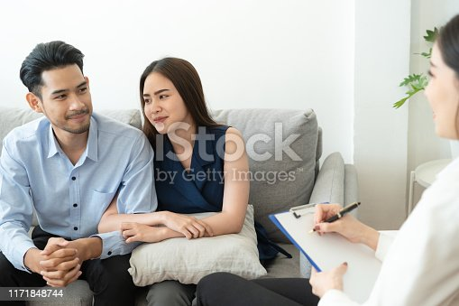 istock Asian couple sitting on the couch in the room to consult mental health problems by doctor, Health and illness concepts 1171848744