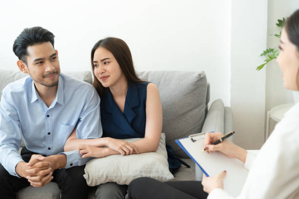 Asian couple sitting on the couch in the room to consult mental health problems by doctor, Health and illness concepts Asian couple sitting on the couch in the room to consult mental health problems by doctor, Health and illness concepts asian couple arguing stock pictures, royalty-free photos & images